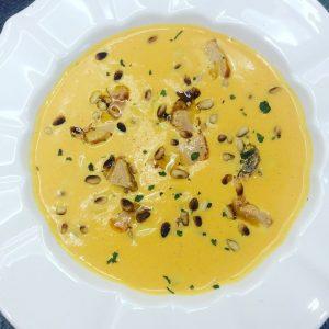 assiette de velouté de potiron au foie gras et pignons avec quelques herbes