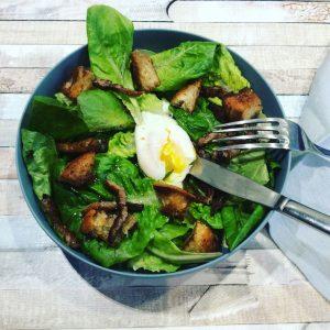 bol de salade lyonnaise avec un oeuf mollet et des croutons