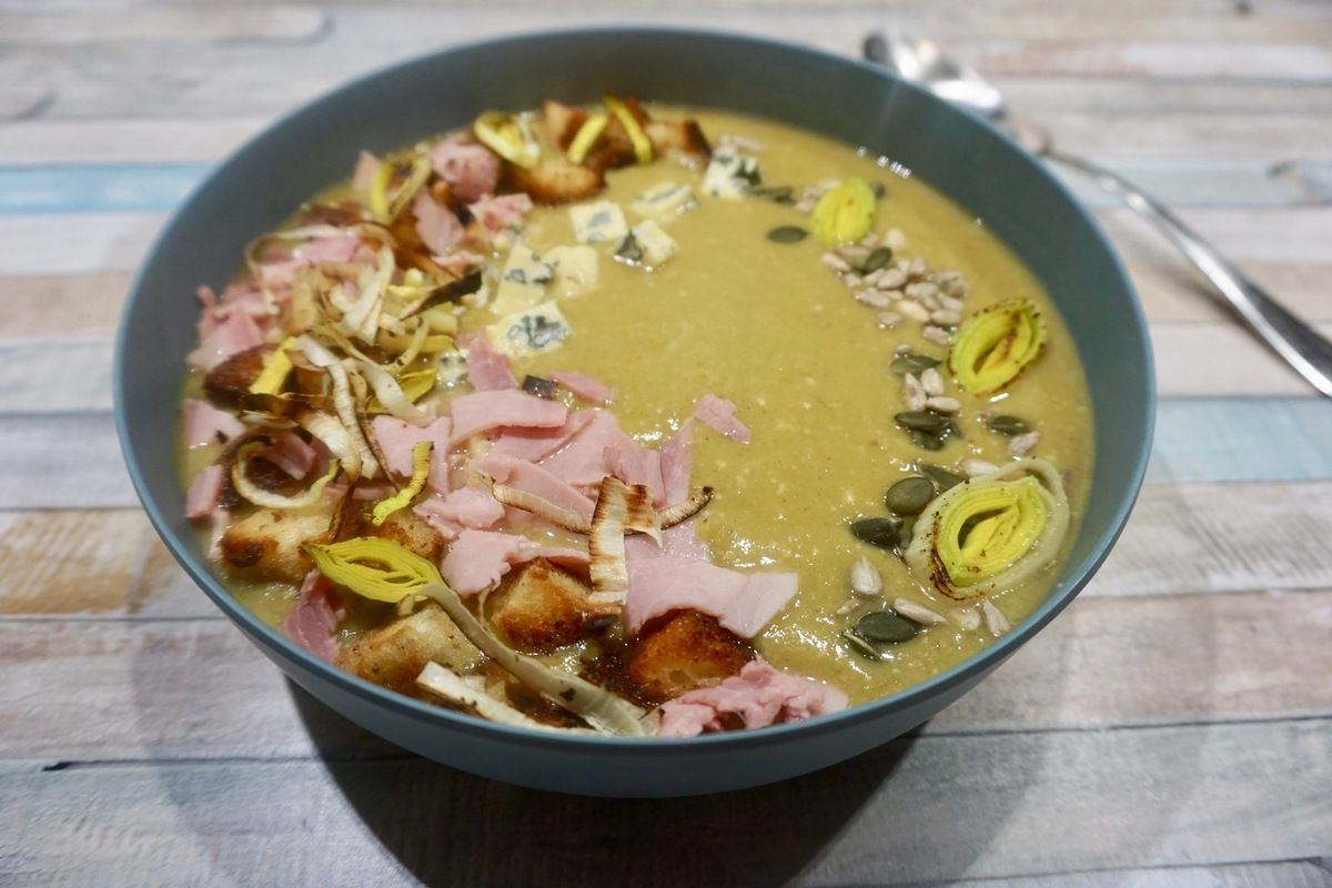 soupe de poireaux garnie de croutons, de cubes de fromage bleu, de morceaux de jambon, de graines de courges et de pignons de pin