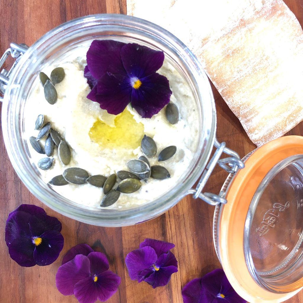 bocal de caviar d'artichaut avec des graines de courge et des fleurs violettes en déco