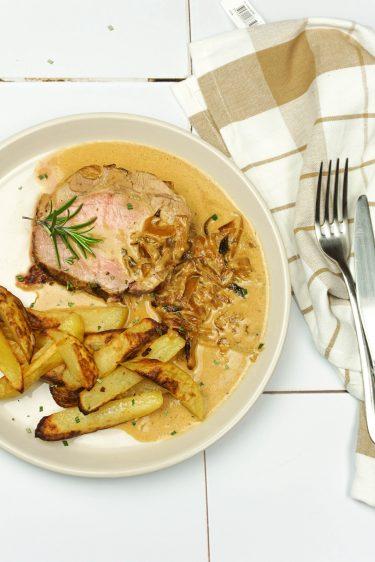 assiette de rôti de porc aux oignons confits et sauce moutarde avec des frites