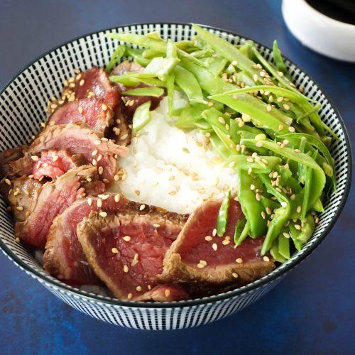 bol de tataki de boeuf avec riz à sushi, fines tranches de viande et poids gourmands