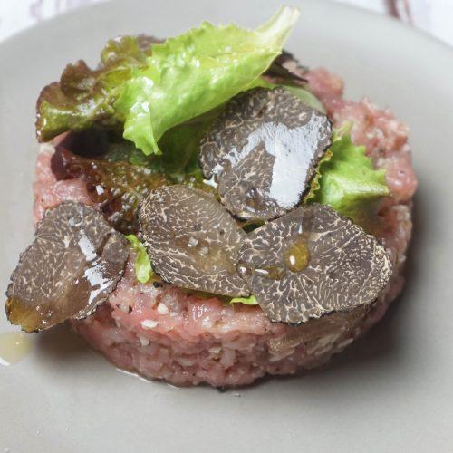 tartare de veau à la truffe avec des lamelles de truffes dessus et quelques feuilles de salade verte